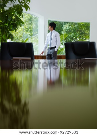 Pensive young asian business man looking out of the window in meeting room window. Side view, copy space - stock photo