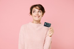 Pensive young brunette woman 20s wearing knitted casual sweater posing isolated on pastel pink background studio portrait. People lifestyle concept. Hold credit bank card, biting lips, looking up