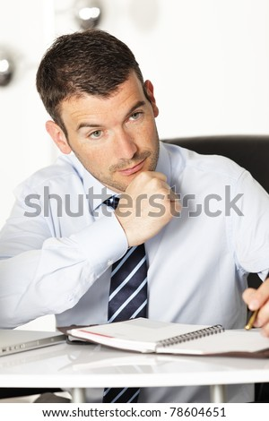 pensive young businessman with pen in office