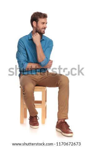pensive young casual man looks to side while sitting on wooden chair on white background