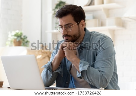 Pensive young Caucasian man in glasses sit at desk look at laptop screen thinking pondering, thoughtful millennial male in spectacles work at computer consider ideas solving problems at home workplace