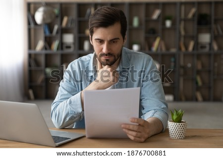Pensive young Caucasian man sit at desk at home work on laptop read paper document. Thoughtful millennial male distracted from computer job consider post paperwork or letter correspondence news. Сток-фото ©