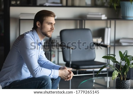 Pensive young Caucasian man sit on chair look in distance thinking or pondering over problem solution, thoughtful male employee lost in thoughts, make plan or decision, have dilemma at workplace Stock fotó ©