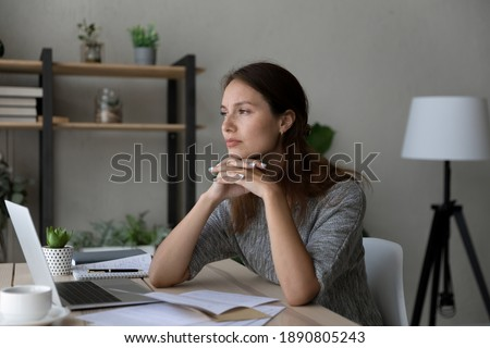 Pensive young Caucasian woman distracted form computer work read letter thinking pondering of problem. Thoughtful millennial female receive unpleasant news in document paperwork, make decision. Foto d'archivio ©