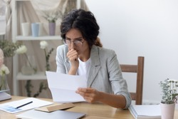 Pensive young Caucasian woman in glasses read message in paper correspondence, think analyze, thoughtful female sit at desk feel stressed confused consider unpleasant notice in paperwork letter