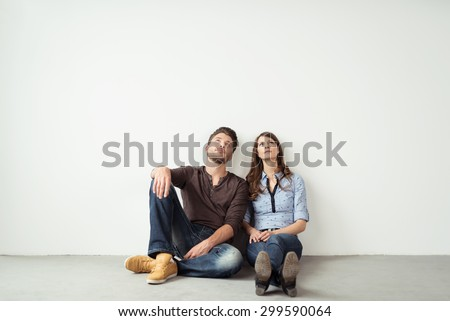 Pensive Young Couple Sitting on the Floor And Looking Up Against Empty White Wall Background with Copy Space.