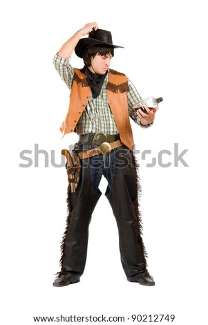 Pensive young cowboy with a bottle of whiskey in hand
