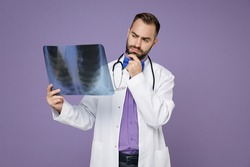 Pensive young doctor man in medical gown stethoscope hold X-ray of lungs fluorography roentgen put hand prop up on chin isolated on violet background. Healthcare personnel health medicine concept