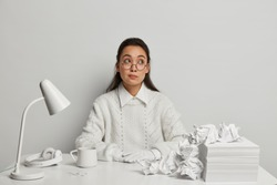 Pensive young female secretary wears big round glasses, white knitted jumper and gloves, looks aside, thinks deeply about something, has much crumpled papers, headphones and desklamp on desktop