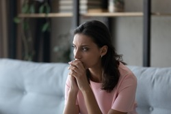 Pensive young indian Arabic woman sit on sofa look in distance thinking or pondering, have personal life problems. Thoughtful millennial ethnic female feel anxious worried. Trouble, stress concept.