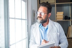 Pensive young male caucasian doctor in white medical uniform look in window distance thinking or pondering, serious man GP plan future career or success in medicine, visualize at workplace writing