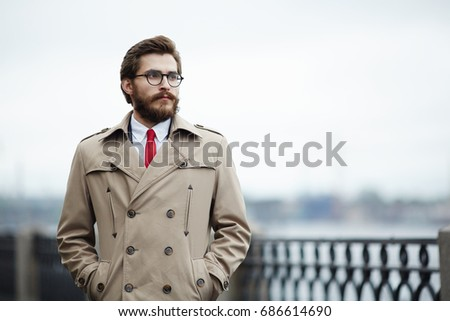 Pensive young man in beige trenchcoat hanging around outdoors Stock photo ©