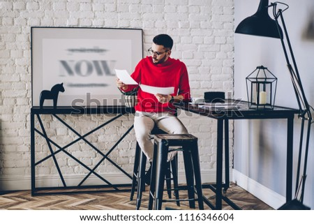 Pensive young man in eyeglasses reading paper documents sitting on chair at desktop in modern apartment with stylish interior.Hipster guy dressed in casual wear checking bills at home #1116346604