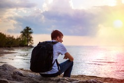 Pensive Young Man on the shore at the Sunset
