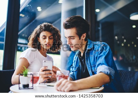 Pensive young man showing how to install app on smartphone girlfriend sitting together at coffee table in modern cafe.Hipster guys watching video in blog on mobile phone using 4G internet