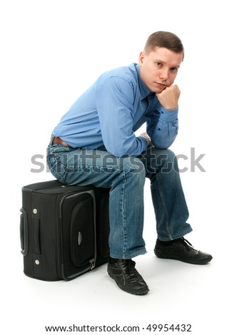 Pensive young man sitting on a hand bag. Isolated on white background