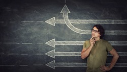 Pensive young man stands over chalkboard background with multiple straight arrows sketches, one of them changes direction bending by upwards trajectory. Different thinking concept, breaking the rules