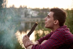 Pensive young man with a burning log in a cloud of smoke on the lake.Copy space.