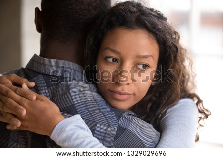 Pensive young mixed race girlfriend think of something hugging boyfriend making peace after fight, worried black woman doubt in relationships, embracing with beloved. Couple distrust, cheating concept