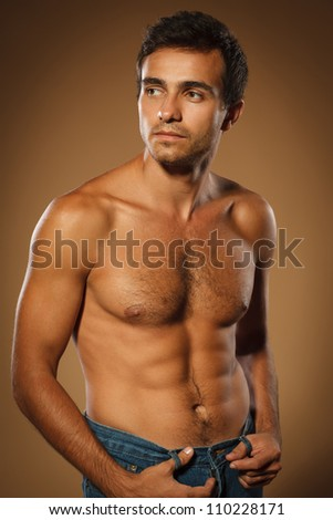 Pensive young muscular male shirtless standing over brown background looking to the side