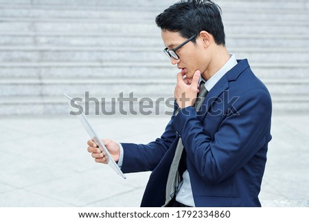 Pensive young Vietnamese entrepreneur in glasses rubbing chin and reading e-mail on tablet computer stock photo
