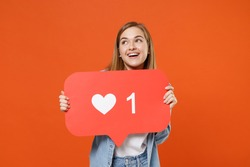 Pensive young woman 20s in casual denim clothes posing isolated on orange wall background. People lifestyle concept. Mock up copy space. Hold huge like sign from social network heart form looking up