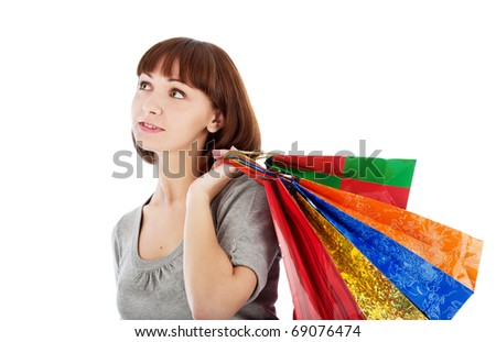 Pensive young woman with colored shopping bags, isolated on white