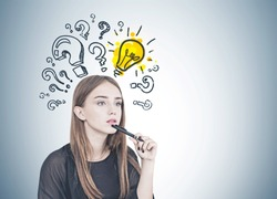 Pensive young woman with long fair hair holding a pen near her chin. Question marks and a light bulb drawn on a gray wall behind her. Mock up
