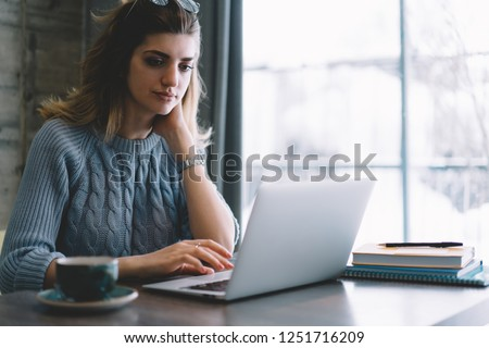 Pensive young woman working on freelance at modern laptop device using wireless internet.Concentrated hipster student searching information on website on computer device sitting in cafe interior #1251716209