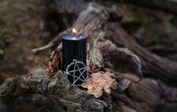 Pentagram amulet and black candle in autumn forest. Magic esoteric witches ritual. Mysticism, divination, wicca, occultism, witchcraft concept. Samhain sabbat, Halloween holiday