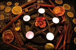 Pentagram with tealights and beautiful christmas yule background for real witch
