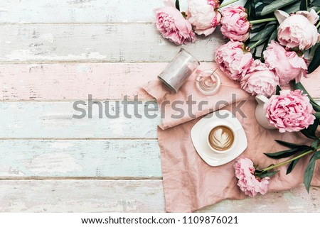 Peony flowers and coffee cup on shabby chic background. Top view