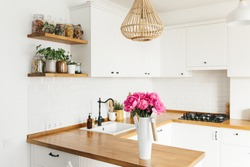Peony flowers in vase on clean white kitchen in modern style, kitchen details. Sustainable living eco friendly kitchen