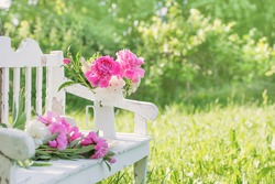 peony in jug on white wooden bench in summer garden