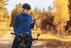 People, active lifestyle and technology. Cyclist on mountain bike using navigation app on smartphone, exploring map in fall forest. Copy space