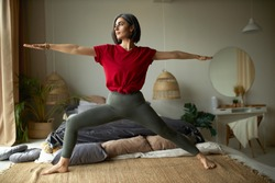 People, activity, health and vitality concept. Stylish barefoot young woman exercising at home, doing vinyasa flow yoga in her bedroom, standing on carpet in virabhadrasana or warrior II pose