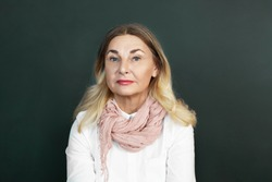 People, age and lifestyle concept. Picture of beautiful Caucasian retired woman with loose blonde colored hair, blue eyes and wrinkles posing in studio, wearing stylish mustard scarf over white blouse