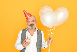 People, age, celebration and holiday concept. Horizontal shot of grumpy elderly businessman posing isolated with balloons, cone hat and cupcake, celebrating his retirement, having displeased look