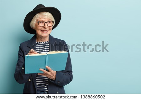 People, age, free time concept. Glad senior female on pension writes list to do in her blue notepad, smiles positively while looks with dreamy expression aside, wears formal apparel, stands indoor #1388860502