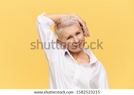 People, aging, maturity, beauty, skin care and health concept. Studio shot of beautiful stylish mature female with pixie dyed haircut bending head and holding hand on cheek doing exercises, smiling