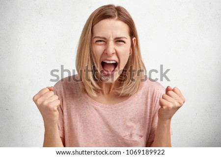 People and aggression concept. Irritated young female model with bobbed hairdo, dressed in casual clothing, clenches fists in anger, has quarrel with husband, poses in studio againt white background