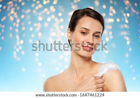 people and beauty concept - beautiful woman with feather touching her shoulder skin over holidays lights on blue background