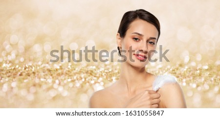 people and beauty concept - beautiful woman with feather touching her shoulder skin over shimmering golden glitter on background