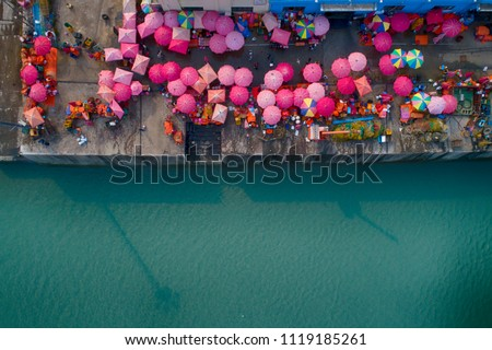 People and colorful umbrellas on fish market