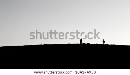 People and dogs silhouettes on a hill in night light, family walking in dark evening, evening darkness and people walking on a hill, small people silhouettes on night on the hill, family, activities
