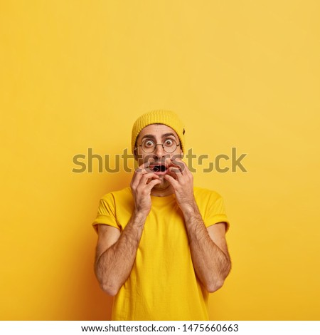 People and emotions concept. Shocked stupefied adult man reacts on terrible shocking news, gasps from fear, keeps mouth opened, dressed in vivid yellow clothes, stands indoor, popps brown eyes