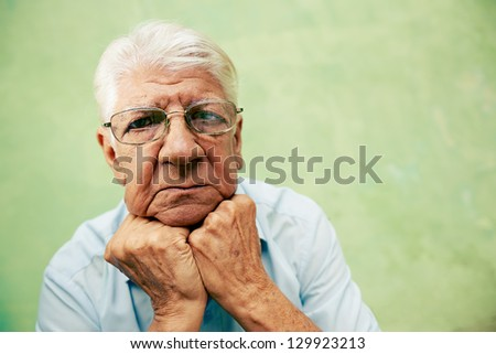 people and emotions, portrait of depressed senior hispanic man with glasses looking at camera, leaning with hands on chin. Copy space
