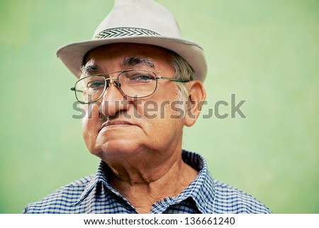 people and emotions, portrait of serious senior hispanic man with glasses and hat looking at camera against green background