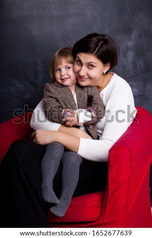 People and family concept. Happy smiling girl with mother hugging on armchair