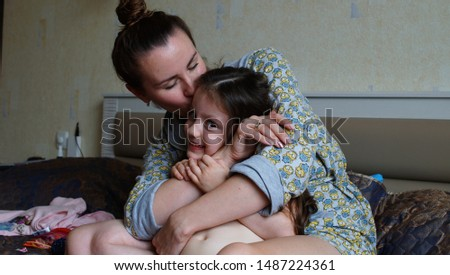 People and family concept - happy smiling girl with mother hugging on sofa at home. Mom kiss daughter